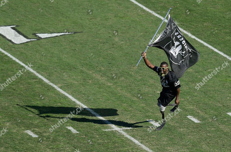 U.S. Paralympic athlete Blake Leeper runs with an Oakland Raiders flag during an NFL football game between the Raiders and the Denver Broncos in Oakland, Calif