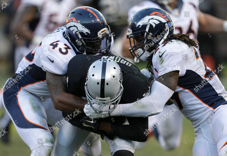 T.J. Ward, Bradley Roby, Vincent Brown Denver Broncos strong safety T.J. Ward (43) and cornerback Bradley Roby tackle Oakland Raiders wide receiver Vincent Brown during the fourth quarter of an NFL football game in Oakland, Calif