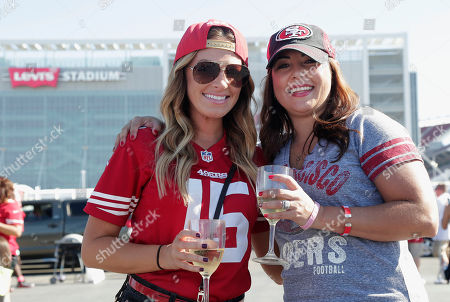 San Francisco 49ers fans Kelly Timko, left, and Tricia Raymond pose for photographs in the Levi's Stadium parking lot before an NFL football game between the 49ers and the Kansas City Chiefs in Santa Clara, Calif