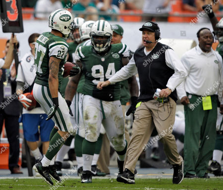 New York Jets head coach Rex Ryan, right, and nose tackle Damon Harrison (94) rush out to greet cornerback Dee Milliner after he interrupted a pass by Miami Dolphins quarterback Ryan Tannehill during the third quarter of an NFL football game, in Miami Gardens, Fla