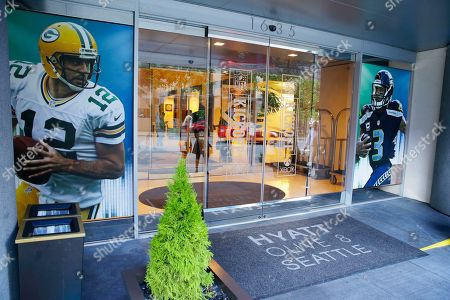 Photos of Seattle Seahawks quarterback Russell Wilson, right, and Green Bay Packers quarterback Aaron Rogers, left, are displayed on the front entryway at the Hyatt at Olive 8 hotel in downtown Seattle