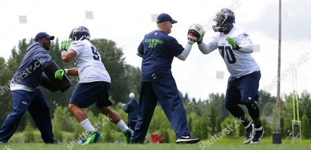 Dan Quinn Seattle Seahawks defensive line coach Travis Jones, left, and defensive coordinator Dan Quinn, third from left, work with Seahawks defensive tackles Jordan Hill, second from left, and Michael Brooks, right, during an NFL football organized team activity, in Renton, Wash