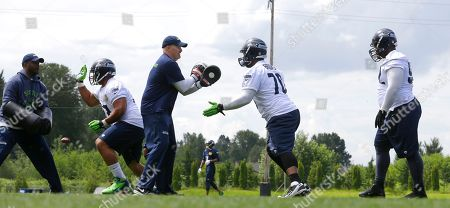 Dan Quinn Seattle Seahawks defensive line coach Travis Jones, left, and defensive coordinator Dan Quinn, third from left, work with defensive tackles, from second from left, Jordan Hill, Michael Brooks and Brandon Mebane during an NFL football organized team activity, in Renton, Wash