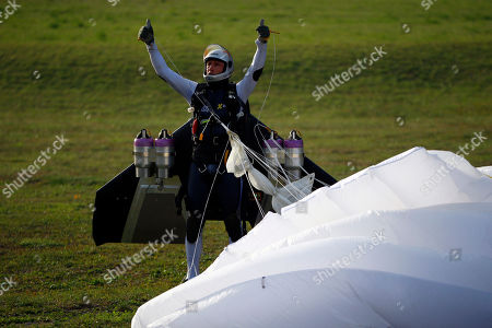 """Swiss pilot Yves Rossy, known as 'Jetman,' the first man in the world to fly a jet-fitted wing, reacts after landing with his parachute during a performance flight during the 43rd Icare Cup paragliding festival in Saint Hilaire du Touvet, French Alps, . The """"Coupe Icare"""" dedicated to free flight, orchestrates all the various types of flying such as hang gliding, paragliding and acrobatic sailplaneing"""