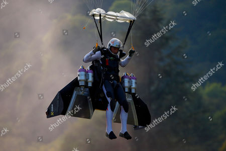 """Stock Photo of Swiss pilot Yves Rossy, known as 'Jetman,' the first man in the world to fly a jet-fitted wing, prepares to land with his parachute during a performance flight during the 43rd Icare Cup paragliding festival in Saint Hilaire du Touvet, French Alps, . The """"Coupe Icare"""" dedicated to free flight, orchestrates all the various types of flying such as hang gliding, paragliding and acrobatic sailplaneing"""