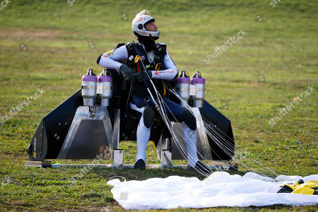 """Swiss pilot Yves Rossy, known as 'Jetman,' the first man in the world to fly a jet-fitted wing, looks on after landing with his parachute during a performance flight during the 43rd Icare Cup paragliding festival in Saint Hilaire du Touvet, French Alps, . The """"Coupe Icare"""" dedicated to free flight, orchestrates all the various types of flying such as hang gliding, paragliding and acrobatic sailplaneing"""