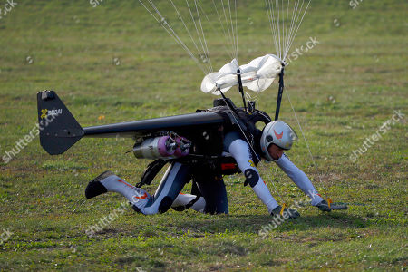 """Stock Picture of Swiss pilot Yves Rossy, known as 'Jetman,' the first man in the world to fly a jet-fitted wing, lands with his parachute during a performance flight during the 43rd Icare Cup paragliding festival in Saint Hilaire du Touvet, French Alps, . The """"Coupe Icare"""" dedicated to free flight, orchestrates all the various types of flying such as hang gliding, paragliding and acrobatic sailplaneing"""