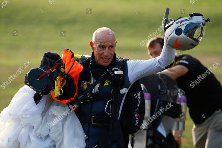 """Stock Image of Swiss pilot Yves Rossy, known as 'Jetman,' the first man in the world to fly a jet-fitted wing, waves to the public after landing with his parachute during a performance flight during the 43rd Icare Cup paragliding festival in Saint Hilaire du Touvet, French Alps, . The """"Coupe Icare"""" dedicated to free flight, orchestrates all the various types of flying such as hang gliding, paragliding and acrobatic sailplaneing"""