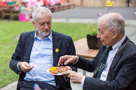 Jeremy Corbyn and Frank Field (r) eat pizza breads Corbyn made during a visit to Beaconsfield Community House in Birkenhead, following his victory declaration. The centre provides clothes and food that would otherwise be destined for waste from supermarkets, to local residents in need.