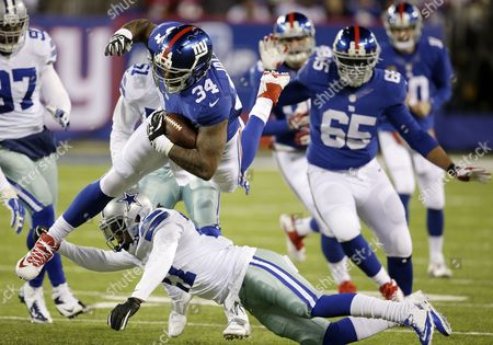 Brandon Jacobs, J.J. Wilcox New York Giants running back Brandon Jacobs (34) leaps over Dallas Cowboys strong safety J.J. Wilcox, bottom, during the second half of an NFL football game, in East Rutherford, N.J