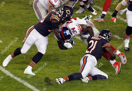 D.J. Williams, Major Wright, Brandon Jacobs Chicago Bears linebacker D.J. Williams (58) and safety Major Wright (21) tackle New York Giants running back Brandon Jacobs (34) In the first half of an NFL football game, in Chicago