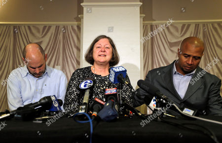 Former NFL player Dorsey Levens, right, extends a hand as Mary Ann Easterling, the widow of former NFL player Ray Easterling, reacts as former NFL player Kevin Turner, left, looks on during a news conference, in Philadelphia, after a hearing to determine whether the NFL faces years of litigation over concussion-related brain injuries. Thousands of former players have accused league officials of concealing what they knew about the risk of playing after a concussion. The lawsuits allege the league glorified violence as the game became a $9 billion-a-year industry