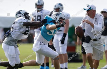 Chase Blackburn, Kenjon Barner Carolina Panthers' Chase Blackburn, center, runs past Kenjon Barner, left, during an NFL football training camp practice in Spartanburg, S.C