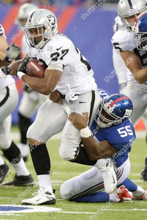 Rashad Jennings, Keith Rivers Oakland Raiders running back Rashad Jennings (27) is tackled by New York Giants outside linebacker Keith Rivers (55) during the first half of an NFL football game, in East Rutherford, N.J