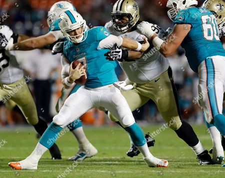 Stock Photo of Pat Devlin, John Jenkins, Nathan Williams Miami Dolphins quarterback Pat Devlin (7) fights a tackle by New Orleans Saints defensive tackle John Jenkins (92) as Dolphins outside linebacker Nathan Williams (6) defends during the second half of an NFL preseason football game, in Miami Gardens, Fla