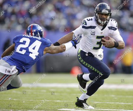 Russell Wilson, Terrell Thomas Seattle Seahawks quarterback Russell Wilson (3) fends off New York Giants cornerback Terrell Thomas (24) during the first half of an NFL football game, in East Rutherford, N.J