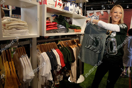 Suzanne Johnson N.Y. Jets owner Woody Johnson's wife, Suzanne, shows off a vintage Jets T-shirt during the grand opening of the NFL Shop at Draft store, in New York