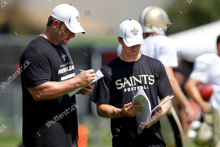 Brian Young, Marcus Ungaro New Orleans Saints defensive assistants Brian Young, left, and Marcus Ungaro, right, read through plays during training camp at their NFL football training facility in Metairie, La