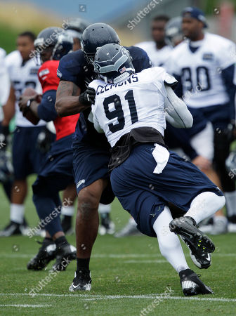 Seattle Seahawks' defensive end Chris Clemons (91) goes up against tackle Alex Barron during practice drills, at NFL football training camp in Renton, Wash