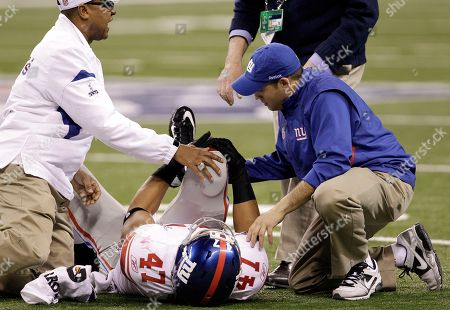 New York Giants tight end Travis Beckum, center, holds his leg as he is tended to by trainers during the first half of the NFL Super Bowl XLVI football game against the New England Patriots, in Indianapolis