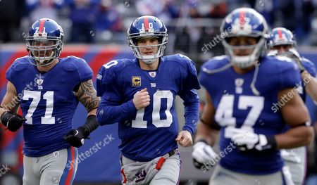 Dave Tollefson, Eli Manning, Travis Beckum New York Giants quarterback Eli Manning (10) runs onto the field with his teammates Dave Tollefson (71) and Travis Beckum before an NFL wild card playoff football game against the Atlanta Falcons, in East Rutherford, N.J