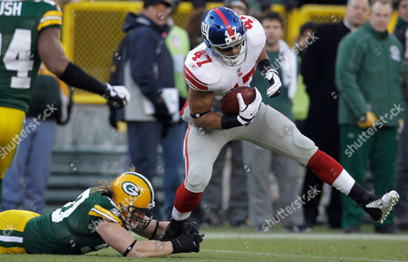 New York Giants tight end Travis Beckum (47) breaks a tackle by Green Bay Packers linebacker A.J. Hawk during the first the first half of an NFL divisional playoff football game, in Green Bay, Wis