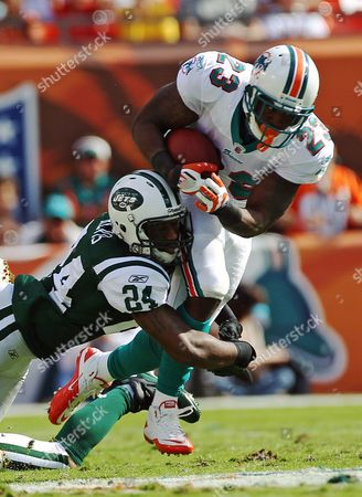 Darelle Revis, Steve Slaton New York Jets' Darrelle Revis (24) tackles Miami Dolphins running back Steve Slaton (23) during the first half of an NFL football game, in Miami. The Dolphins won 19-17