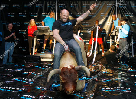 "Randy Couture, DeMarcus Ware, Chad Ochocinco, Ty Murray, Archie Manning, Erin Andrews, Peyton Manning MMA champion Randy Couture, center, rides a mechanical bull during a promotional event by Reebok, in Dallas. Looking on from left is former NFL player Archie Manning, sports reporter Erin Andrews, NFL players Peyton Manning, DeMarcus Ware and Chad Ochocinco and ""King of Rodeo"" Ty Murray"