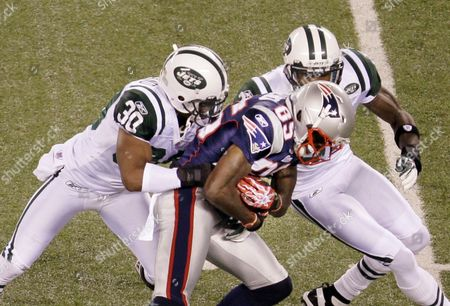 Stock Image of Chad Ochocinco New York Jets defensive back Donald Strickland (30) and Antonio Cromartie (31) tackle New England Patriots wide receiver Chad Ochocinco (85) in the first quarter of an NFL football game in East Rutherford, N.J