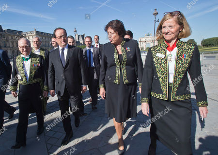 France's President Francois Hollande, 2nd left, walks with members of theFrench academy of science Gabriel de Broglie, left, Catherine Brechignac, 2nd right, and Pascale Cossart as he arrived at the World Science Day a gathering of scientists from 57 countries at the Louvre museum in Paris, . France is also celebrating 350 years of it's academy of science