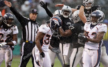 Hiram Eugene, Syd'Quan Thompson Oakland Raiders safety Hiram Eugene, center signaling, celebrates after recovering a fumble by Denver Broncos Syd'Quan Thompson (22) on a punt return in the second quarter of an NFL football game in Oakland, Calif