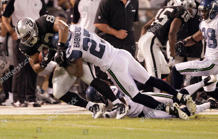 Oakland Raiders tight end John Owens (82) is tackled by Seattle Seahawks safety Jordan Babineaux (27) in the second quarter of an NFL preseason football game in Oakland, Calif