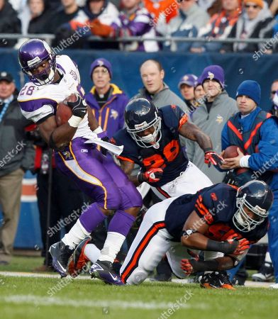 Adrian Peterson, Lance Briggs, Tim Jennings Minnesota Vikings running back Adrian Peterson (28) eludes a tackle by Chicago Bears linebacker Lance Briggs, right, and cornerback Tim Jennings (26) in the first half of an NFL football game in Chicago