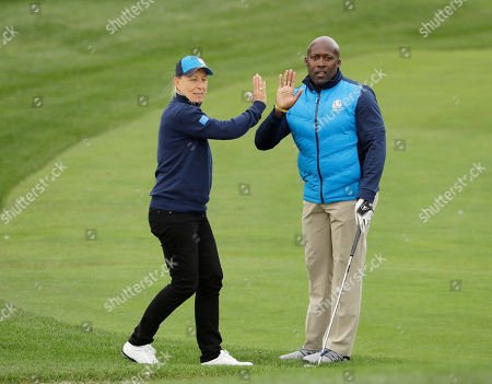 Europe's John Regis and Martina Narvratilova high five during the celebrity match at the Ryder Cup golf tournament, at Hazeltine National Golf Club in Chaska, Minn
