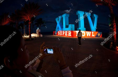 Anna Ortiz has her picture taken in front of a large NFL football Super Bowl XLIV logo along the beach, in Fort Lauderdale, Fla