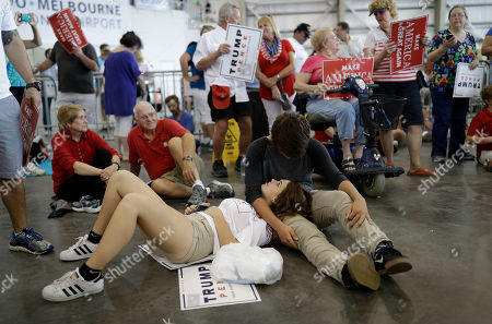 Alexis Taylor rests on Gabe Albert before a rally with Republican presidential candidate Donald Trump, in Melbourne, Fla