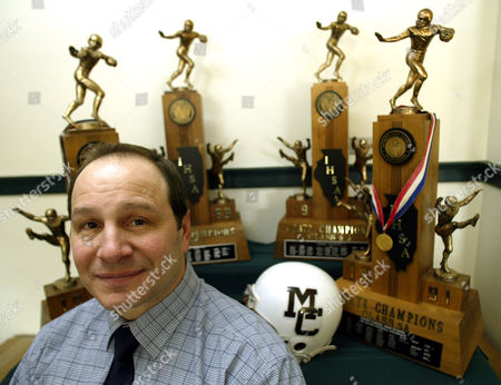 LENTI Mt. Carmel High School head football coach Frank Lenti sits in with trophies from four of the nine state championships his teams have won at Mt. Carmel High School in Chicago. The trophies shown, from the 1988-1991 seasons, represent the years that Tampa Bay Buccaneers defensive end Simeon Rice played for the school. Philadelphia Eagles quarterback Donovan McNabb, and Tennessee Titans wide receiver Darrell Hill are both former Mt. Carmel students and football players, and OaklandRaiders head coach Bill Callahan was once an assistant to Lenti, giving the school representatives on all four of the NFL teams playing in conference championship games this weekend