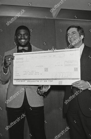 """Lawrence Taylor, left, of the New York Giants, holds an oversized check presented to him by Seagrams Distillers Company representative Joel Weiner in New York on Seagrams awarded Taylor its """"Seven Crowns of Sports"""" trophy, as well as a $5,000 check, naming him as their choice for the top defensive player in the NFL for 1983"""