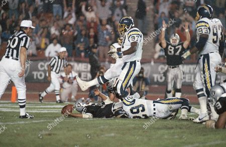 Los Angeles Raiders Marcus Allen falls into the end zone to score during third quarter of NFL game with the San Diego Chargers at the Coliseum, Los Angeles, Calif. Chargers are John Hendy (29) and Tony Simmons (97). Raiders Trey Junkin (87) signals score in background. Raiders won, 34-21