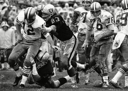 Oakland Raiders' Ben Davidson (83) and Tom Keating, on ground, get to San Francisco 49ers quarterback John Brodie during an NFL football game in Oakland, Calif. The play was called back and San Francisco was penalized for illegal procedure. Davidson, the hulking defensive end who starred for the Raiders in the 1960s before becoming a famous television pitch man, died . He was 72