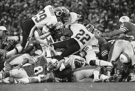 Stock Image of Miami Dolphins quarterback David Woodley (16) is at the conter of a mass of Washington Redskins defenders during Super Bowl XVII action in the Rose Bowl in Pasadena, Calif. Adding to the confusion around Woodley are 'Skins Mark Murphy (29), Curtis Jordan (22) and Dave Butz (65). Redskins won, 27-17