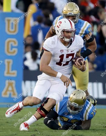 Stock Photo of Stanford quarterback Ryan Burns runs past UCLA defensive lineman Boss Tagaloa during the first half of an NCAA college football game in Pasadena, Calif