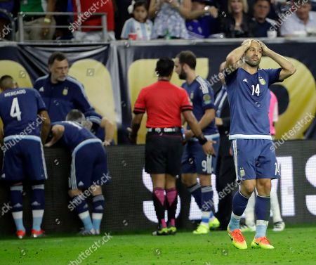 Argentina midfielder Javier Mascherano (14) reacts after teammate forward Ezequiel Lavezzi takes a fall over the sideline during a Copa America Centenario semifinal soccer match against the United States, in Houston