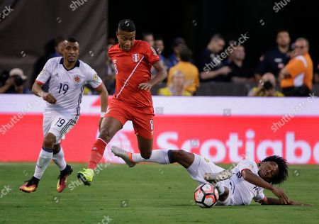 Colombia's Juan Cuadrado, right, slides to try to pick the ball from Peru's Andy Polo (8) as Colombia's Farid Diaz (19) looks on during the first half of a Copa America Centenario quarterfinal soccer match, in East Rutherford, N.J