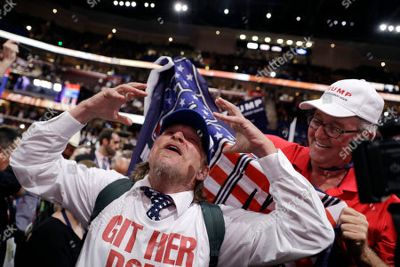 "Jake Byrd, Bob Hayssen Tony Barbieri reacts as the character ""Jake Byrd"" from the ""Jimmy Kimmel Live!"" show as New York delegate Bob Hayssen holds up a Trump flag during the second day session of the Republican National Convention in Cleveland"