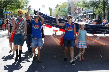 U.S. Army veteran Sarah Alder, left, her partner Joyce McCall, center-right, and their daughter Lydia help carry a giant American flag in the gay pride parade, in Denver