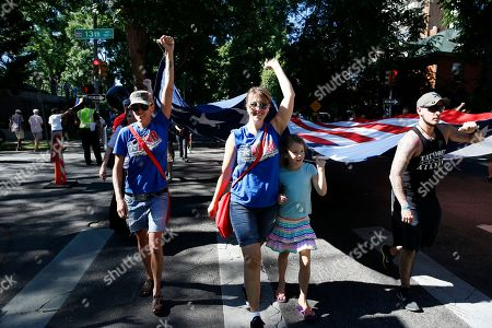 U.S. Army veteran Sarah Alder, left, her partner Joyce McCall, second from left, and their daughter Lydia help carry a giant American flag in the gay pride parade, in Denver