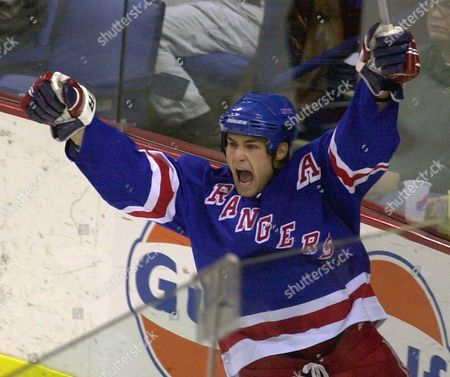 Stock Image of New York Rangers center Eric Lindros celebrates after assisting teammate Michael York on the Rangers' fourth goal of the game during the third period against the Buffalo Sabres at the HSBC Arena in Buffalo, N.Y. Lindros is finally a Hockey Hall of Famer. Lindros was elected, as part of the class of 2016 that also features Soviet star Sergei Makarov and goaltender Rogie Vachon. The late Pat Quinn made it in as a builder