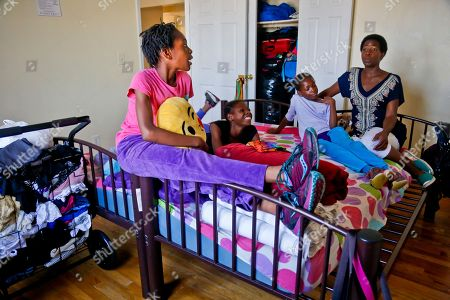 """Tonia Handy, Tai Sheppard, Rainn Sheppard, Brooke Sheppard Tonia Handy, far right, and her daughters, Rainn, 10, far left, Tai, 11, second from left, and Brooke, 8, second from right, together in the bedroom of their apartment in a Brooklyn shelter, in New York. """"Some families meet at the dinner table, we have these mattresses that were put together by two twin beds and that's our meeting place,"""" said Handy. """"We do everything in that bed. It's somewhere to connect"""