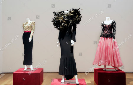 A black feather-embellished gown, center, owned by the late comedian Joan Rivers, is displayed at Christie's, in New York